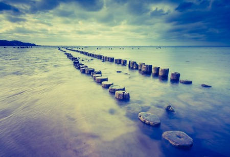 Babie: Vintage photo of beautiful view on Baltic sandy coast with old military buildings from world war II and wooden breakwaters. Long exposure photo Stock Photo