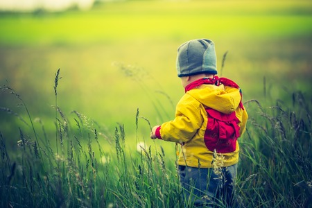 lomography: Vintage photo of small child playing on meadow