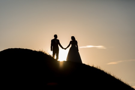 cloud shape: Silhouettes of wedding couple standing on hill in beautiful sunset