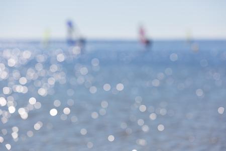 windsurfers: Defocused seascape with windsurfers on sea surface. Blurry landscape useful as background