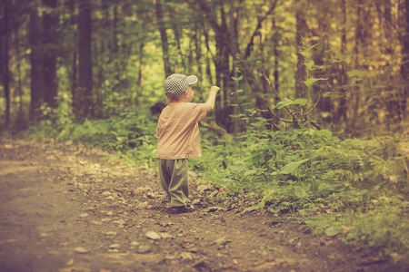 Vintage photo of boy playing in forest. Beautiful childhood spend with nature. 写真素材