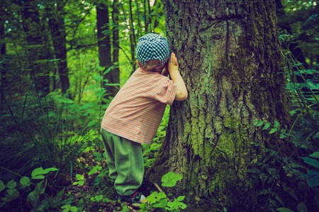 Vintage photo of boy playing in forest. Beautiful childhood spend with nature. Standard-Bild