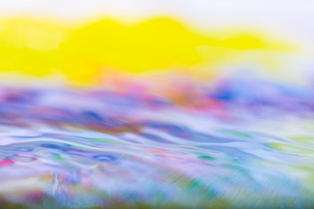 heaving: Moving water abstraction. Close up of water surface with colorful reflections