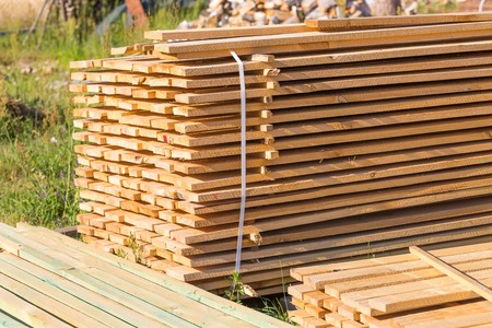 wooden boards: Boards from sawmill for house roof construction. Wooden planks lying in the yard.
