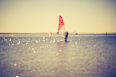 windsurfers: Vintage photo of defocused seascape with windsurfers on sea surface. Blurry landscape useful as background Stock Photo