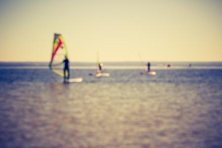 windsurfers: Vintage photo of defocused seascape with windsurfers on sea surface. Blurry landscape useful as background Stock Photo