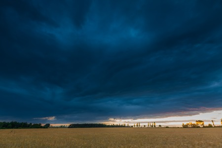 rural countryside: Landscape with dark stormy sky over fields. Beautiful rural countryside at twilight Stock Photo
