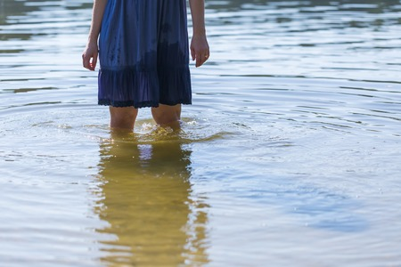 human body part: Close up of legs of girl standing in lake water. Human body part close up.