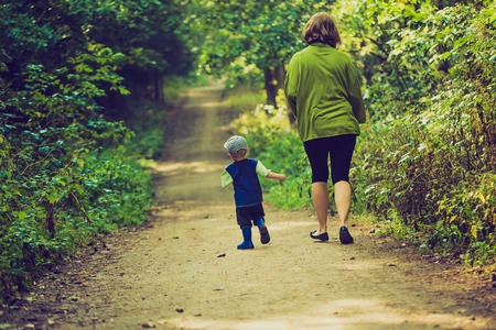 people from behind: Vintage photo of mother with stroller and baby walking by summer forest path. People from behind
