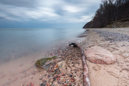 long exposure: Beautiful long exposure landscape of rocky sea shore. Tranquil scene of Baltic sea.