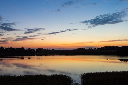 horizon reflection: Beautiful lake landscape after sunset with sky reflected in water. Calm landscape