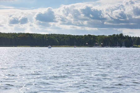 mazury: Yacht or boats on beautiful lake in Mazury lake district. Mamry lake in Poland with sailboats photographed i early autumn. Stock Photo