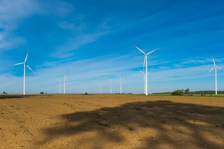 plowed: Plowed fields and wind farm. Beautiful landscape with blue sky over plowed field and windmills.