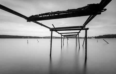 windlass: Long exposure landscape of lake shore with old, destroyed steel construction (windlass for boats). Lake Krzywe in Olsztyn, Poland. Stock Photo