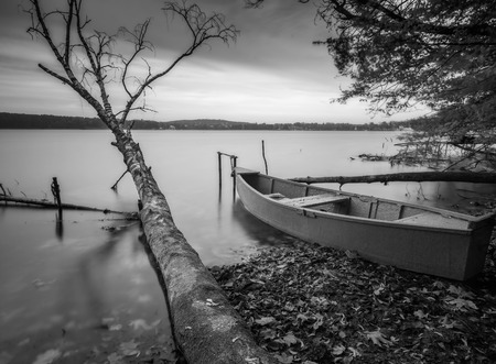 Black and white long exposure landscape of lake shore with moored boats. Lake Krzywe in Olsztyn, Poland.