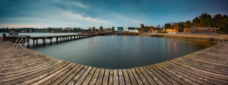 landscape architecture: Panoramic landscape with wooden jetty on city beach of Olsztyn in Poland. Long exposure landscape with architecture elements.