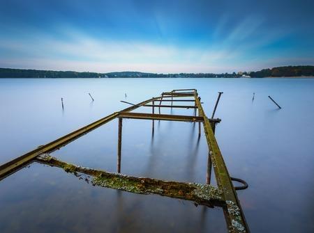 windlass: Long exposure landscape of lake shore with old, destroyed steel construction (windlass for boats). Lake Krzywe in Olsztyn, Poland. Stock Photo