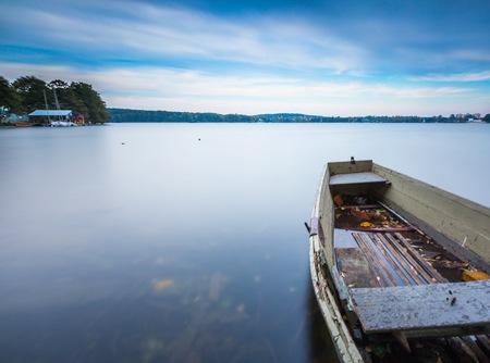 sunset lake: Long exposure landscape of lake shore with moored boats. Lake Krzywe in Olsztyn, Poland. Stock Photo