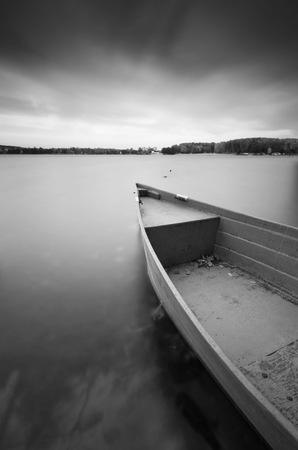 Zwart-wit lange blootstelling landschap van meer kust met afgemeerde boten. Meer Krzywe in Olsztyn, Polen.
