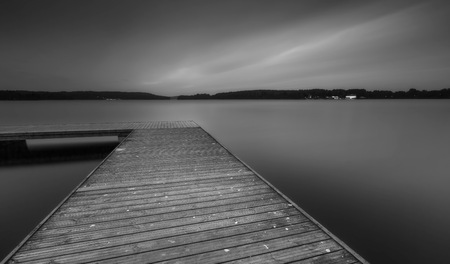 olsztyn: Black and white landscape with wooden jetty on city beach of Olsztyn in Poland. Long exposure landscape with architecture elements. Stock Photo