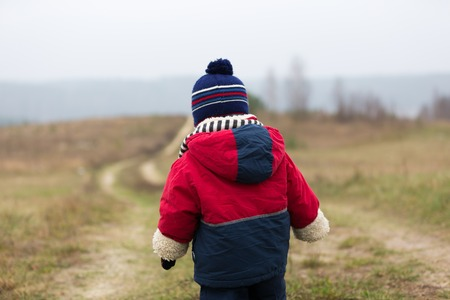 toddler walking: Caucasian child playing outdoor. Toddler walking by rural countryside at late autumn and bad wether