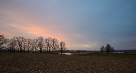 plowed field: Evening sky over plowed field. Autumnal landscape of autumnal field and sunset sky. Stock Photo