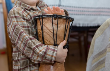 Small child playing on drum. Little caucasian boy and drum. Hands close up