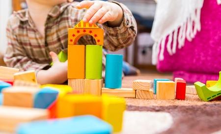 Klein kind spelen met houten blokken. Blanke jongen gebouw met blokken Stockfoto