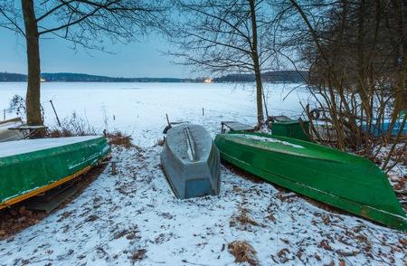 frozen lake: Winter landscape with fisherman boats lying on frozen lake shore. Winter lake landscape