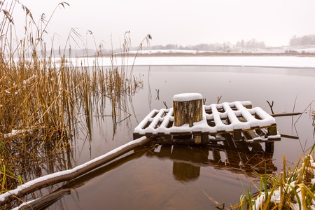 frozen lake: Landscape with jetty covered by snow on frozen lake shore near mouth ov river.