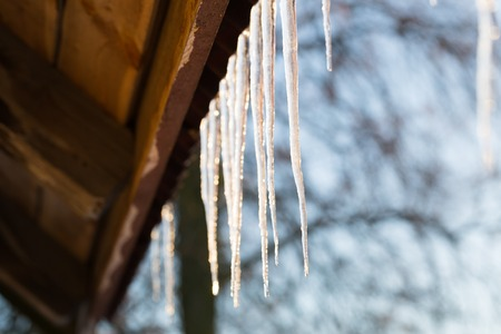 edge of the ice: Icicles hanging on roof at winter. Natural ice formation of ice crystals hanging on roof edge at winter.