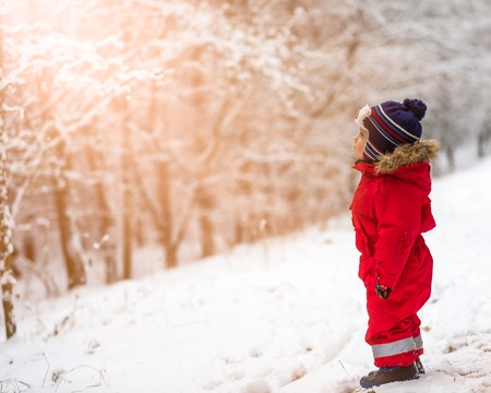 january 1: Small boy playing outdoor in snowy winter landscape.