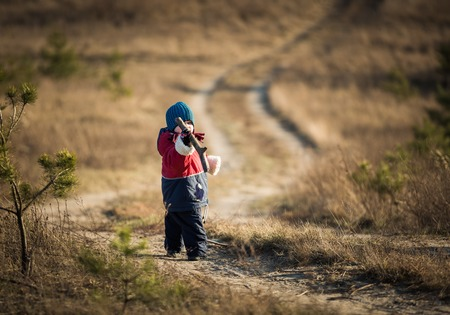 spent: Young happy boy playing outdoor in beautiful rural landscape in golden light at spring. Happy childhood spent in the countryside. Stock Photo