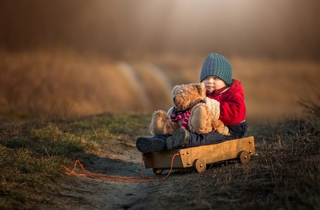 Young happy boy playing with his teddy bear and carriage toy outdoor in beautiful rural landscape in golden light at spring. Happy childhood spent in the countryside. Standard-Bild
