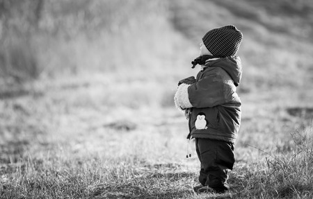 white gloves: Young happy boy playing outdoor in beautiful rural landscape in golden light at spring. Happy childhood spent in the countryside. Black and white Stock Photo