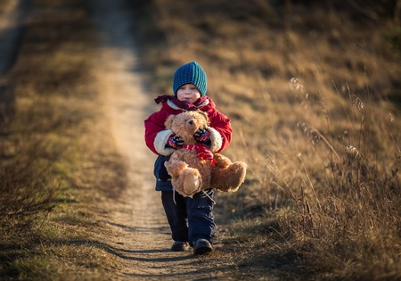 teddy bears: Young happy boy playing with his teddy bear toy outdoor in beautiful rural landscape in golden light at spring. Happy childhood spent in the countryside.