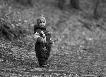 spent: Little boy playing in forest at early spring. Happy childhood spent in ntaure. Caucasian child playing outdoor Stock Photo
