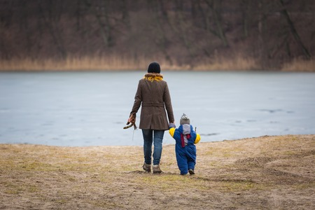 Mother and child walking together in nature with holding hands. Beautiful motherhood. Landscape with people.