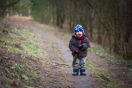 serious face: Little bad boy screaming outdoor near forest. Angry child with serious face. Stock Photo