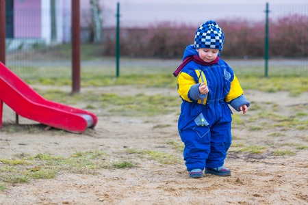 2 years old: Little boy playing outdoor on city playground at early springtime. Happy 2 years old child.
