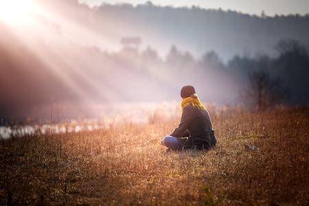 persona triste: Joven mujer sentada sobre la hierba en el prado cerca del lago y el sueño. Foto tomada desde atrás.
