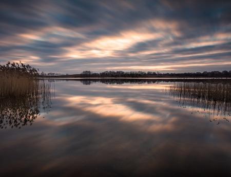 long lake: Lake landscape sunset photographed on long exposure. Polish lake in Mazury lake district. Stock Photo