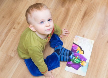 illustrated: Small child (boy) watching a illustrated book. Boy playing with book , watching illustrations.