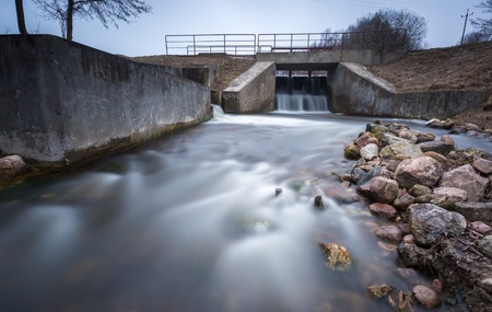 long exposure: Long exposure photo of dam on river. Landscape with building.