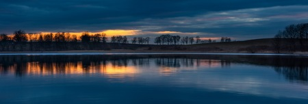 tree line: Lake after sunset landscape. Close up of opposite shore of lake with trees and sky reflected in water. Beautiful landscape. Stock Photo