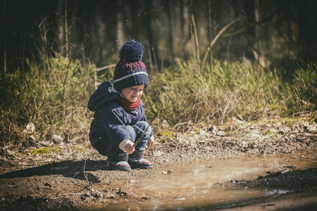 Little boy playing in puddle in spring forest. happy childhood