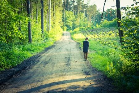 Weinlesefoto des Mädchens gehend durch Waldweg . Frühlingswald mit dem Gehen , das durch Weg geht