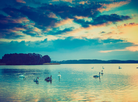 Vintage photo of sunset over calm lake in Poland. Old photo of lake sunset.