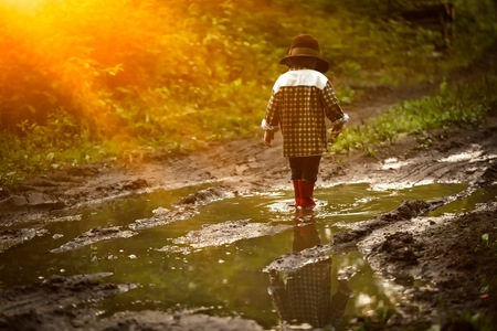 Little boy in hat and rubber shoes playing in puddle in summer forest. Standard-Bild