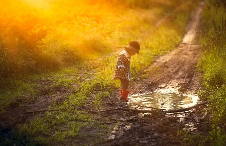Little boy in hat and rubber shoes playing in puddle in summer forest. 免版税图像